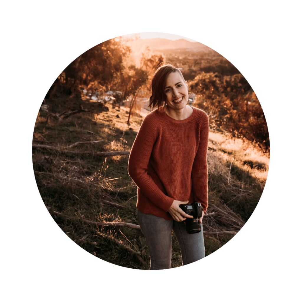 Carris from Captivated Photography wearing a jumper and jeans standing in a paddock holding her camera