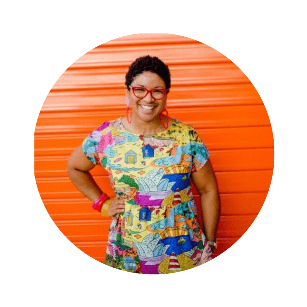 Keneena from Kablooie wearing a bright printed dress green glasses standing in front of a bright orange roller door