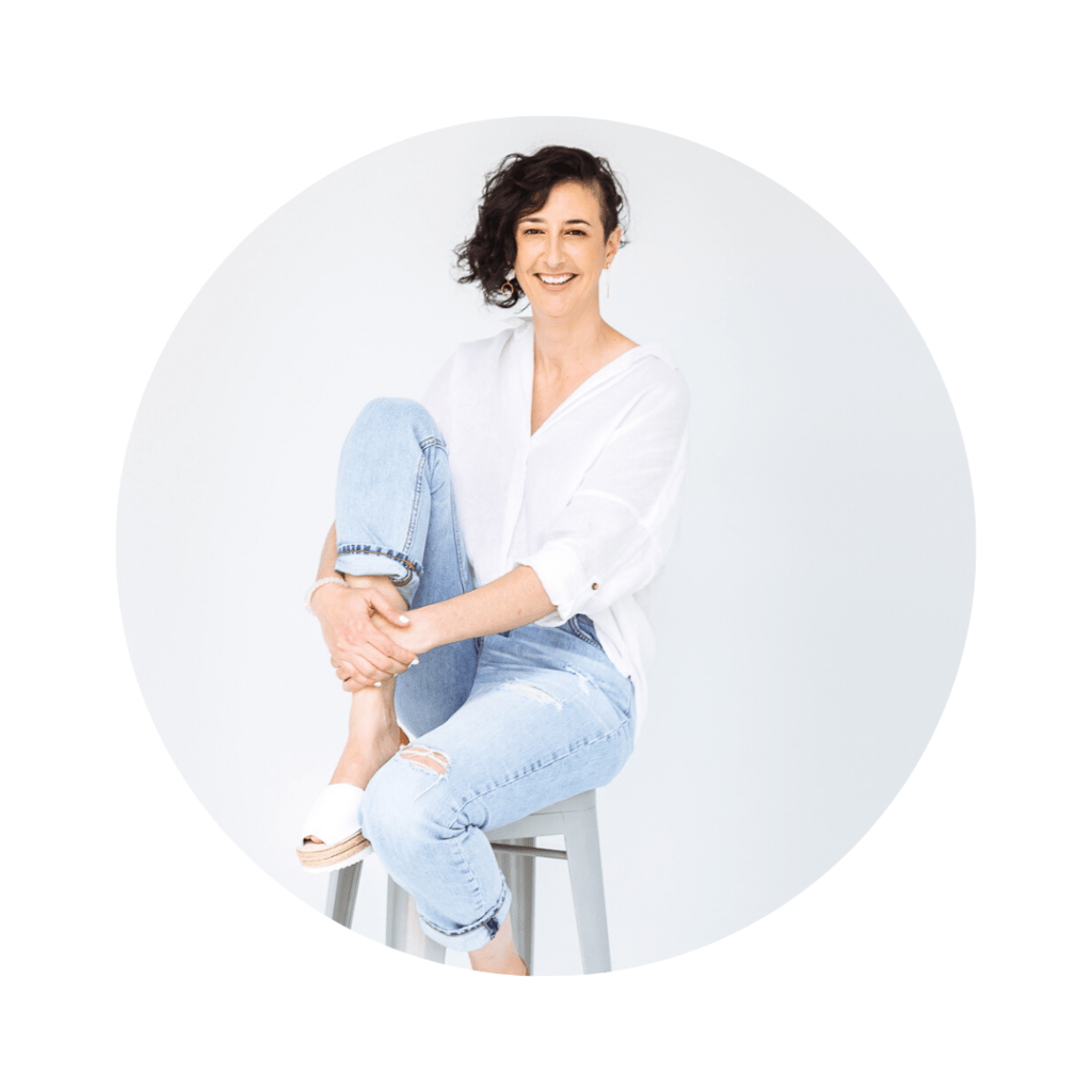 Naomi from Avarcas Australia sitting on a stool wearing a white linen shirt denim jeans and white avarcas
